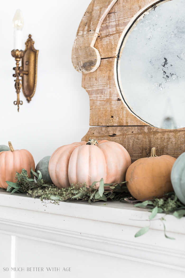 White fireplace mantel with muted colored pumpkins on it and a mirror behind them.
