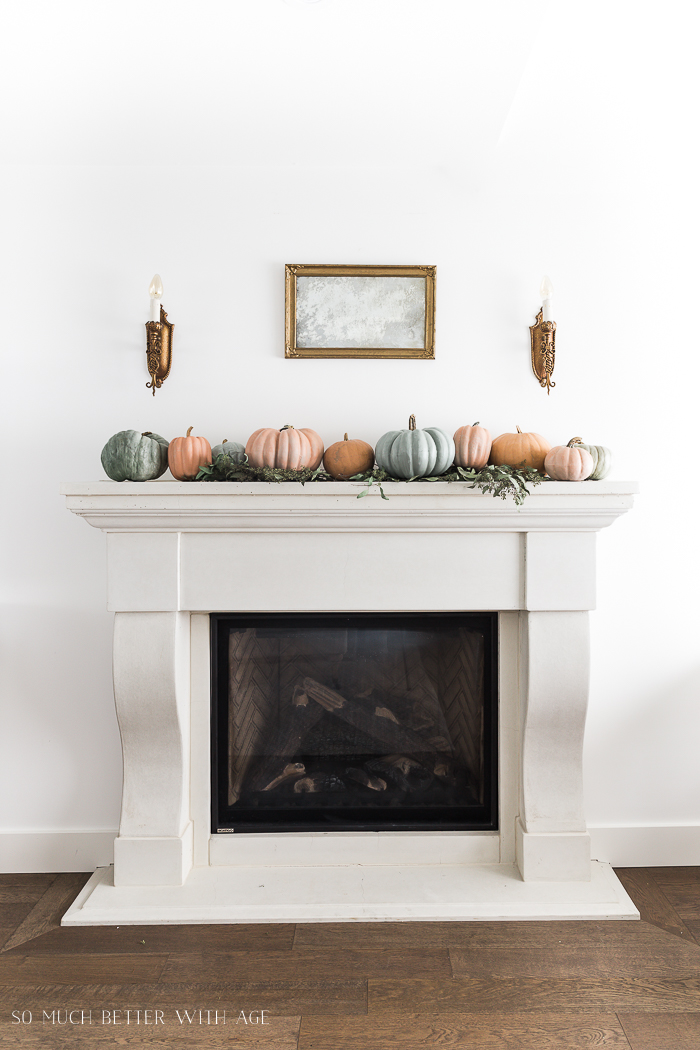 White fireplace mantel with soft colored pumpkins flanked by gold wall sconces.