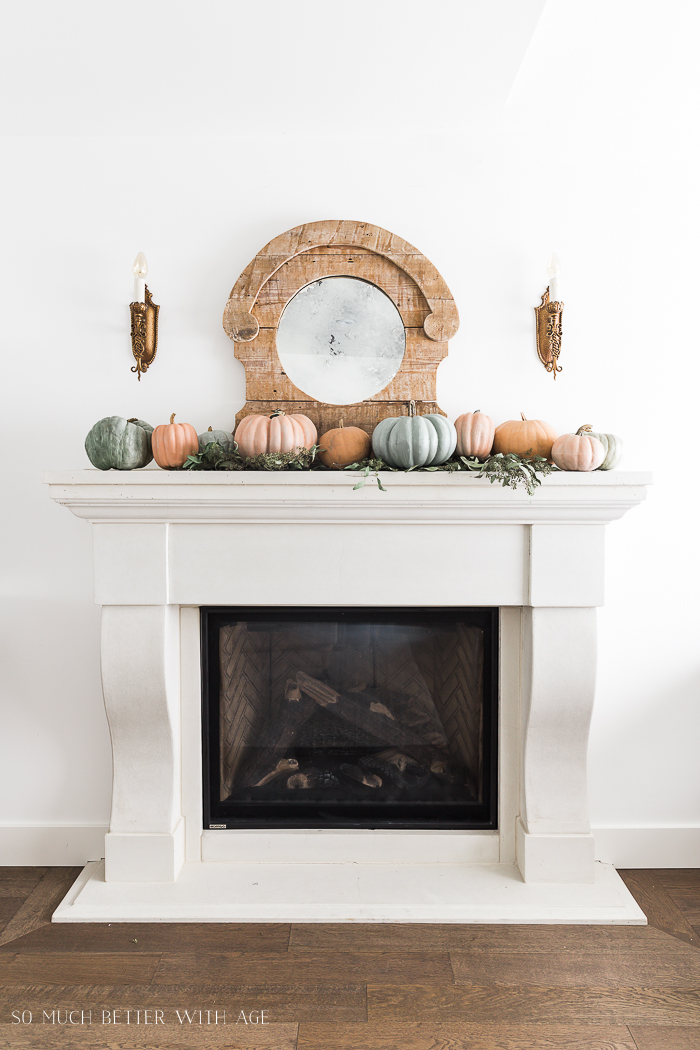Large wooden vintage mirror with the pumpkins on the white mantel.