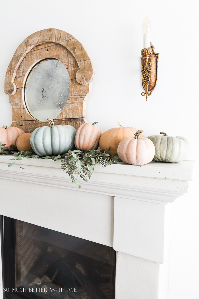 White fireplace mantel with the real and faux pumpkins lined up on it and eucalyptus.