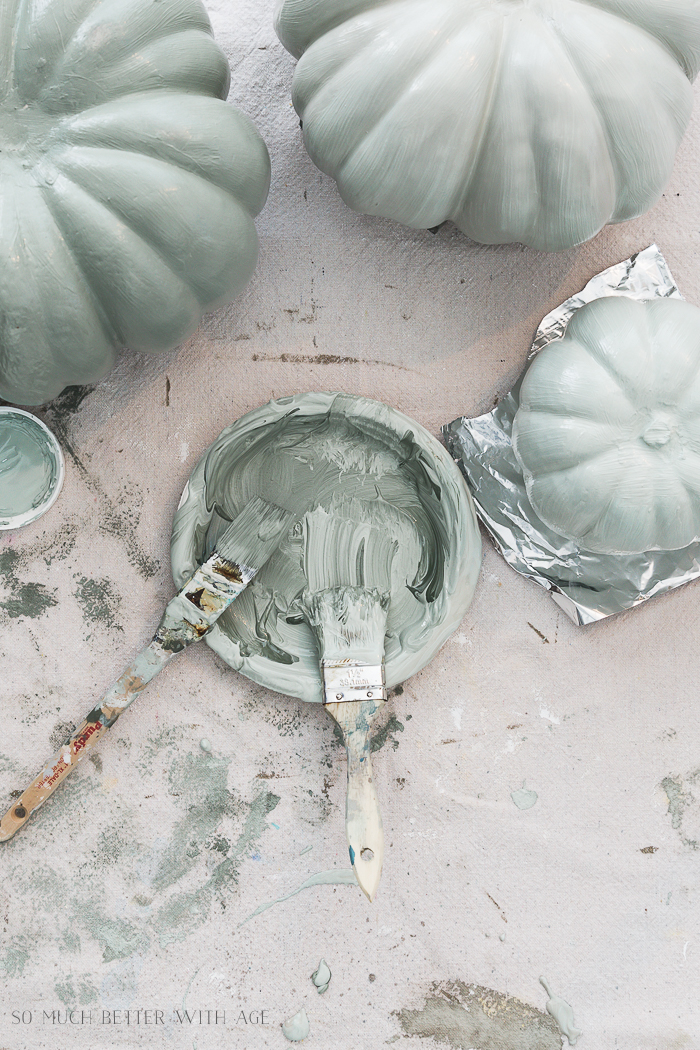 Painting Pumpkins in Muted Colors/sage green paint. with paint brushes on paint tray.