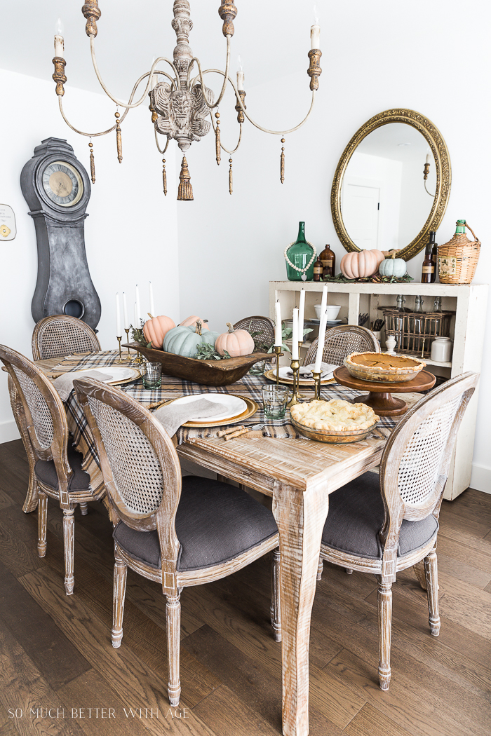Dining room table setting on wood table and wooden chandelier.