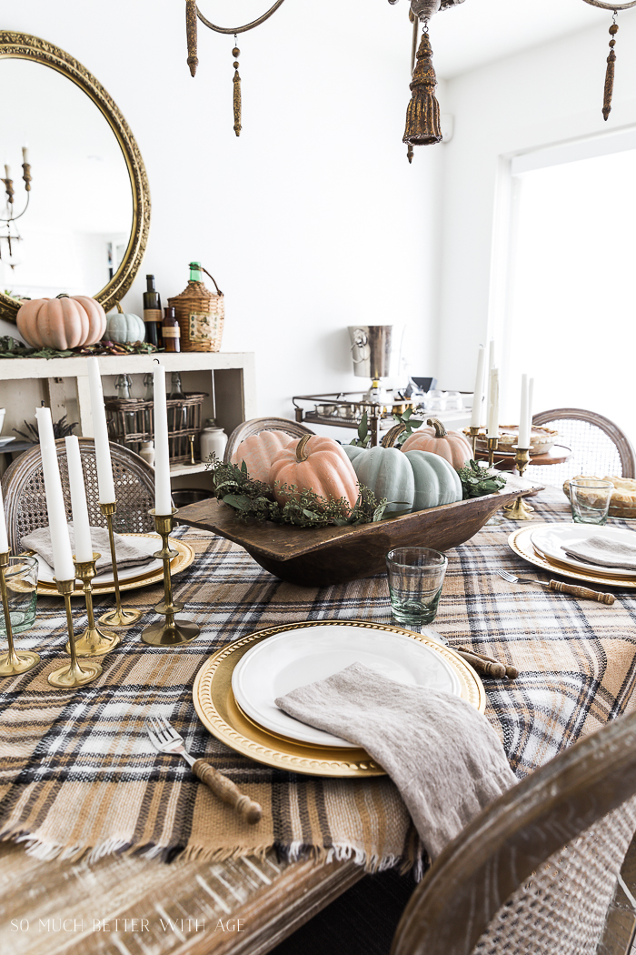White and gold plates on plaid tablecloth.