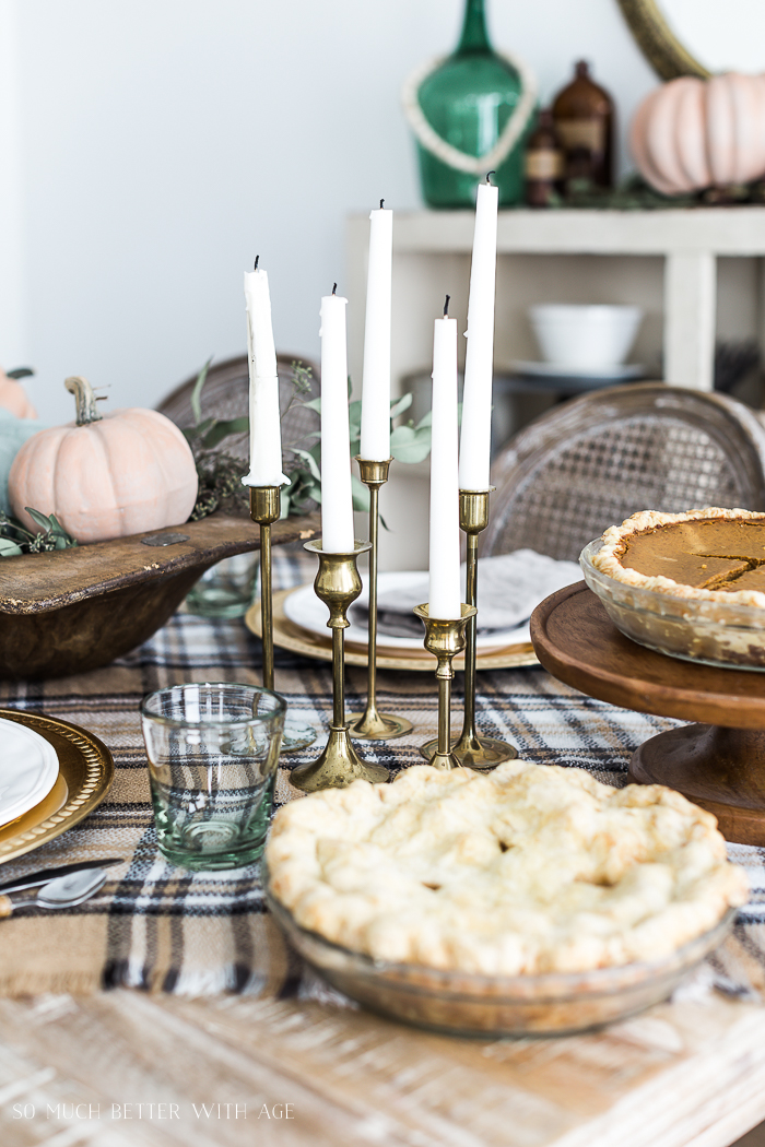 Apple pie and bras candlesticks on table.