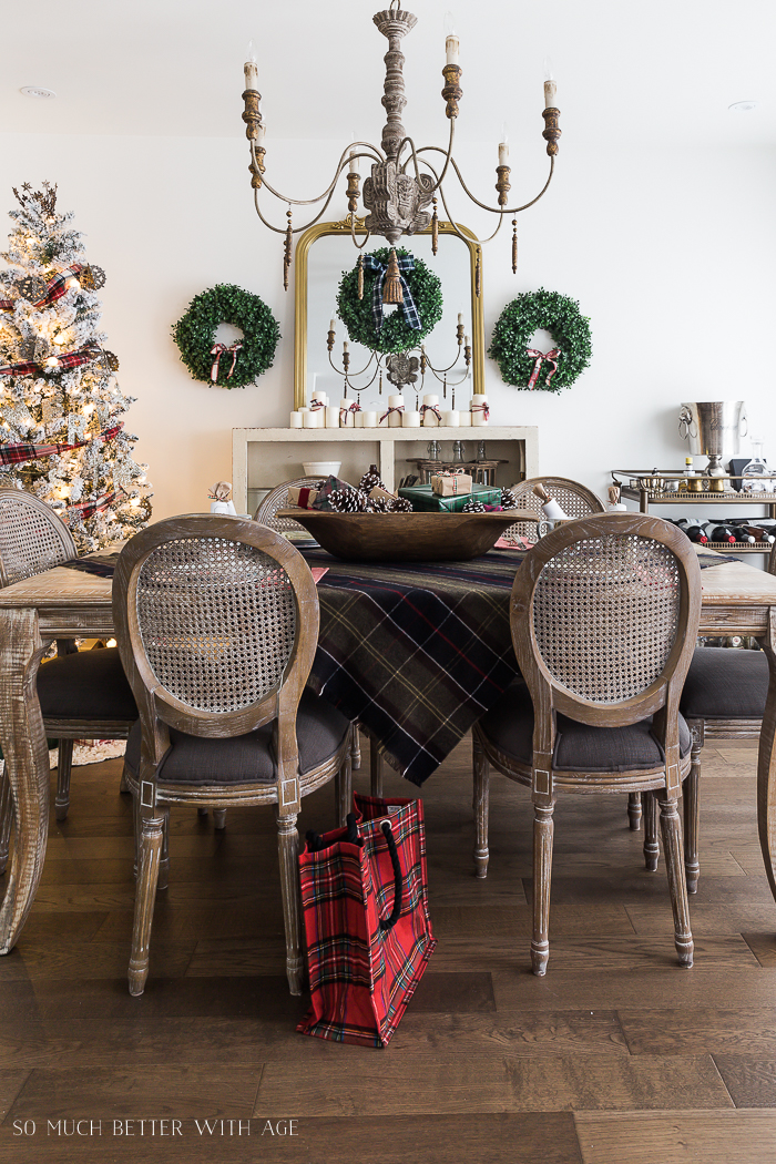 A holiday decor setting in the dining room with mini green wreaths on the wall, plaid tablecloth, a buffalo print bag on the floor.