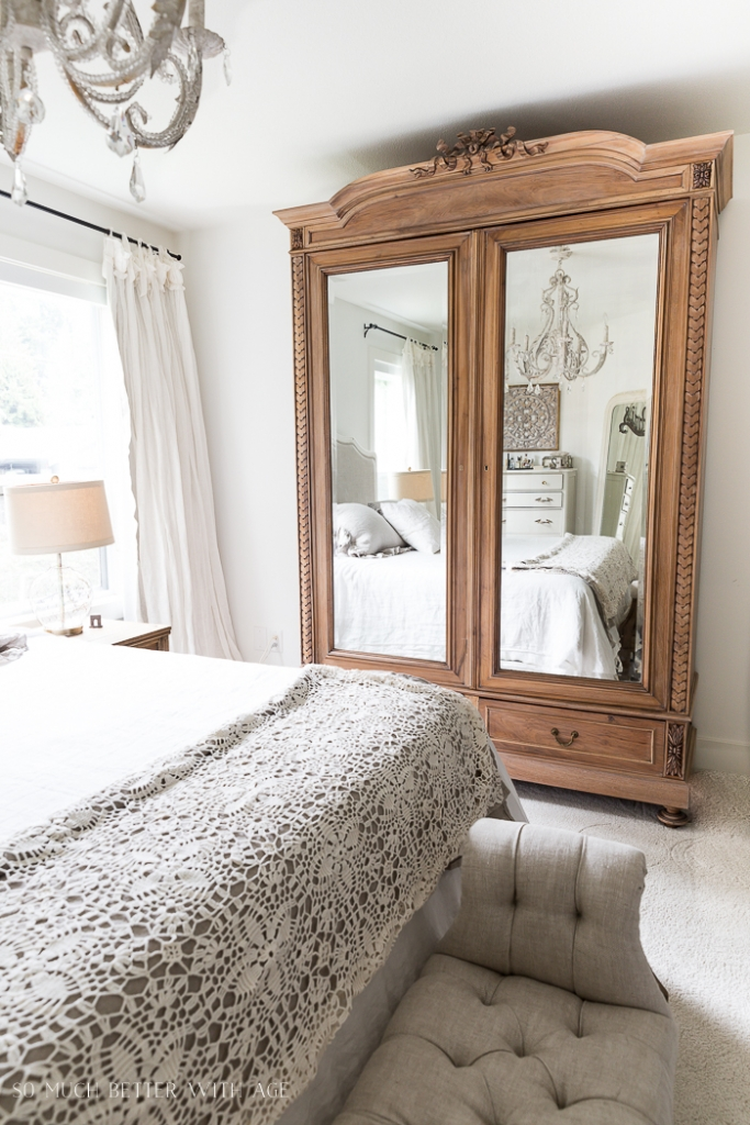 Large wooden armoire in bedroom with white bedding and crystal chandelier.