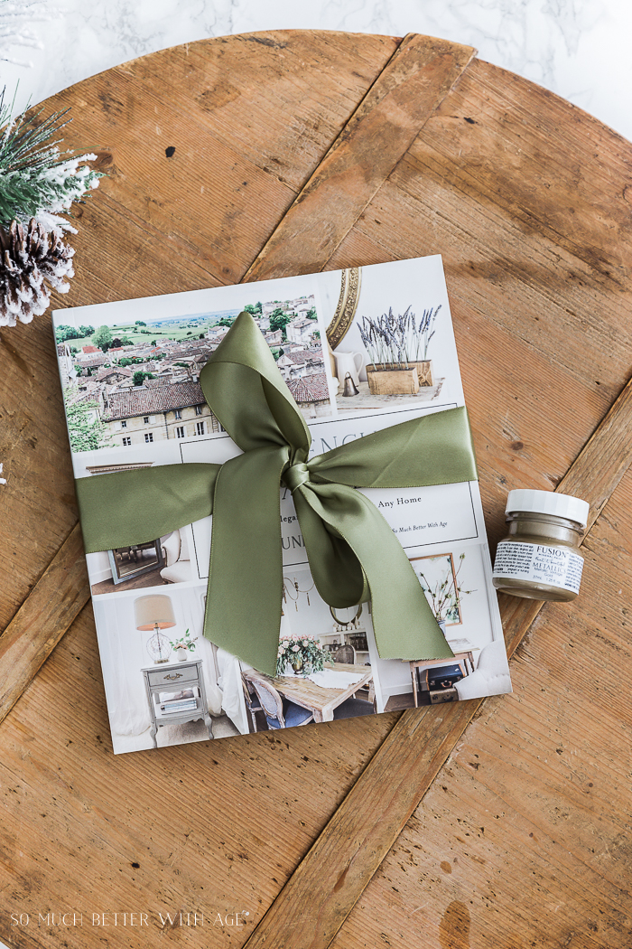A wooden board wth French Vintage Decor book on it with a green bow tied around the book.