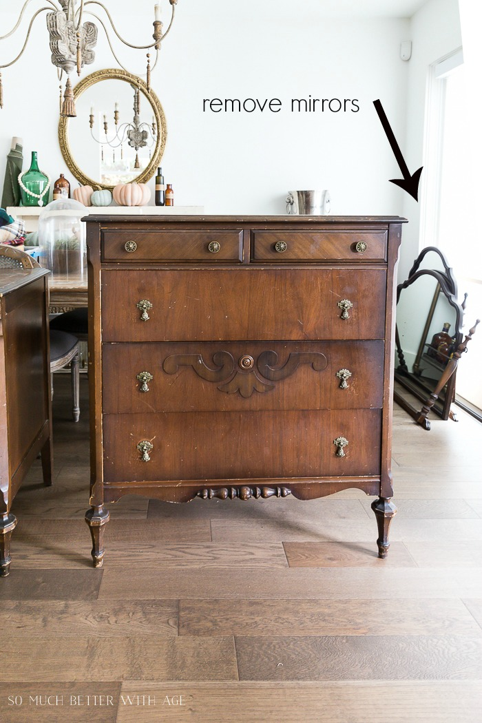 Old wooden dresser with words and an arrow pointing to mirrors on the floor.