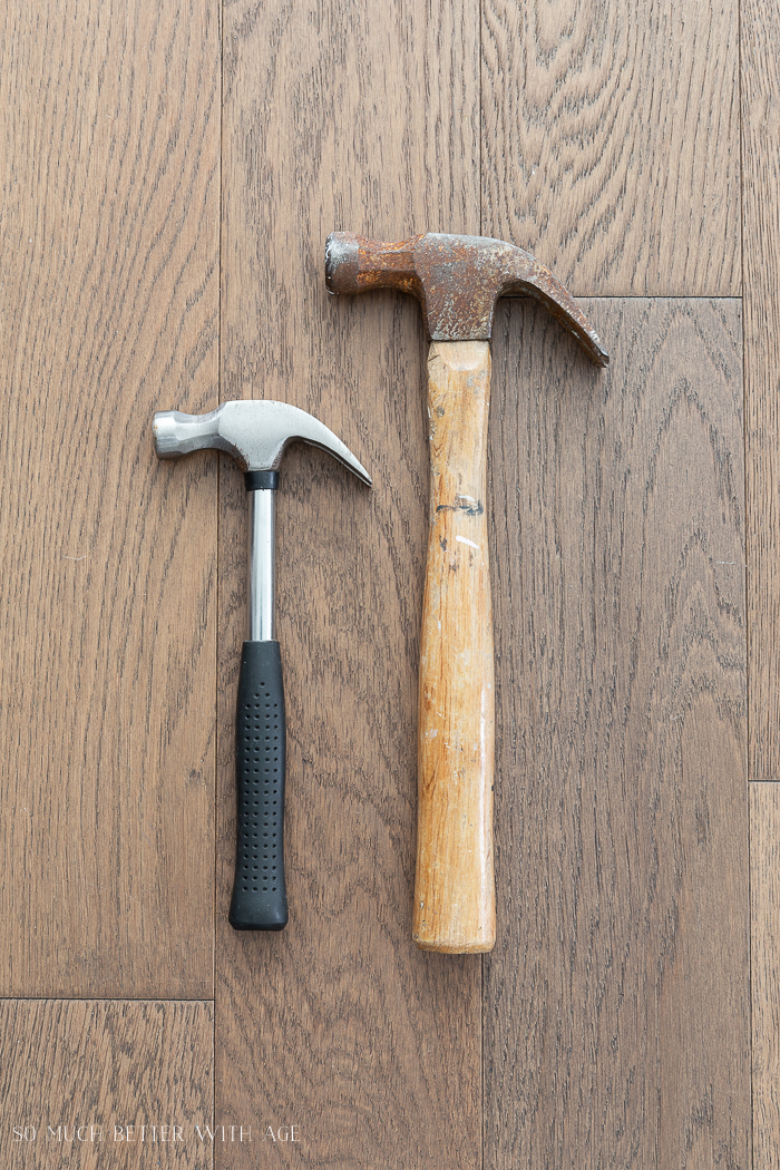 Two hammers lying on the floor side by side.