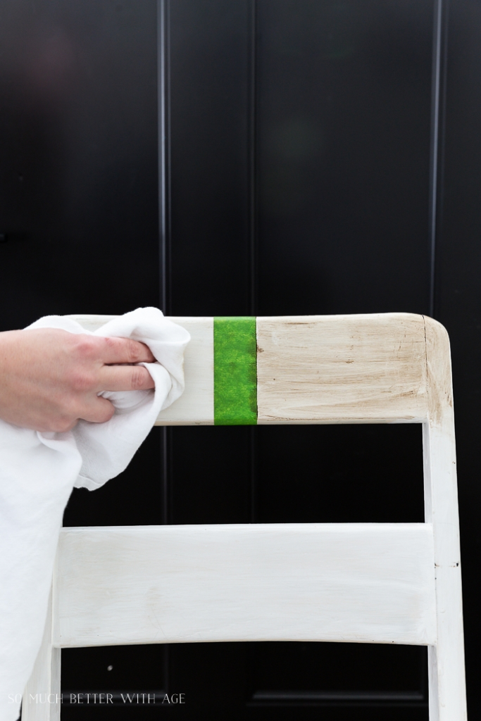 Chair with piece of green tape in middle of back and testing different paints.