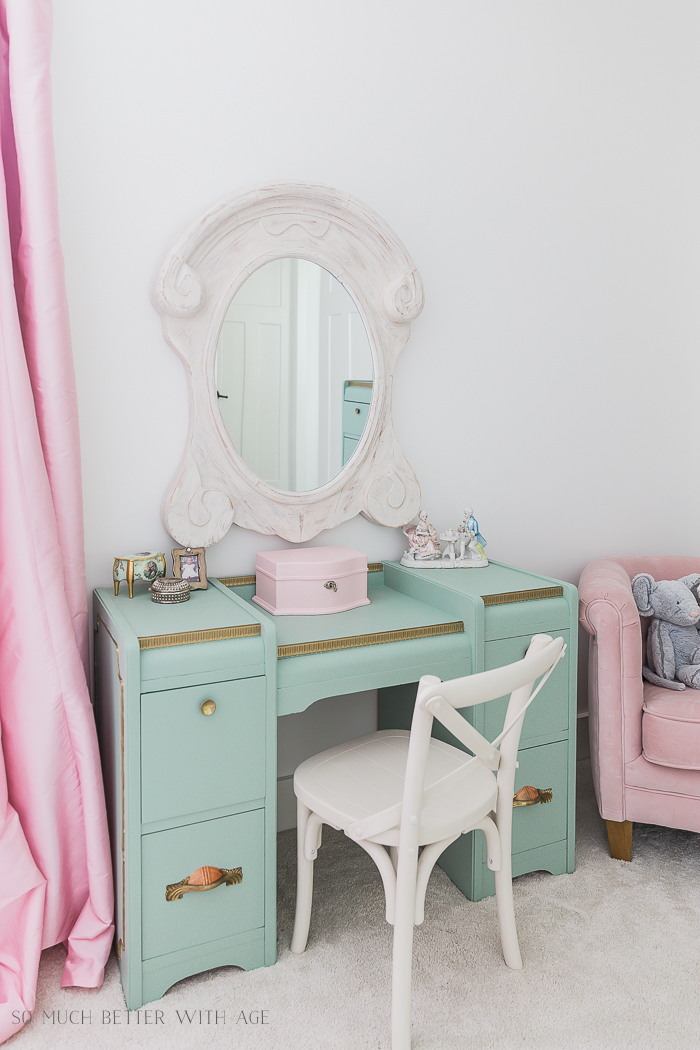Green vanity with white mirror and pink chair.