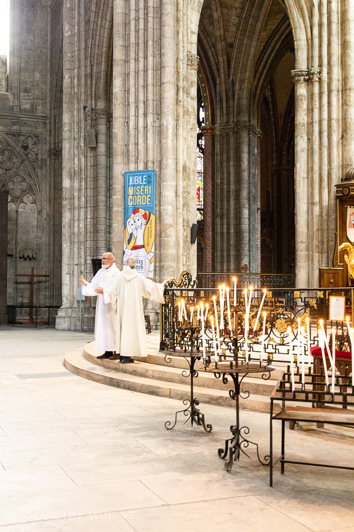The priests on the inside of the church with lit candles.