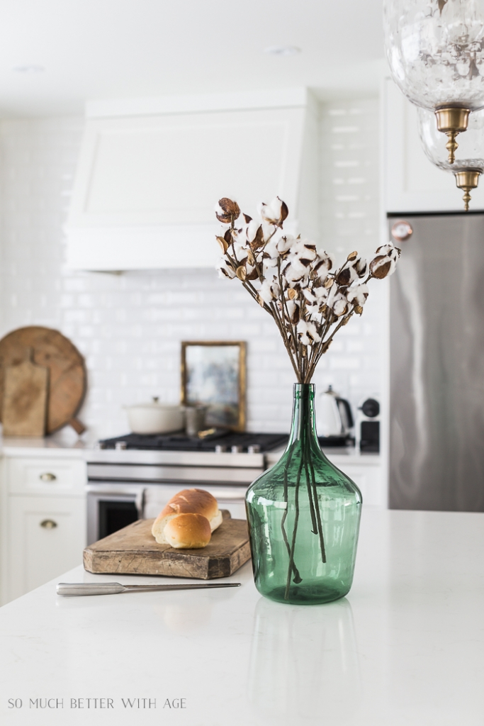 Green demijohn on kitchen island with bread in white kitchen.