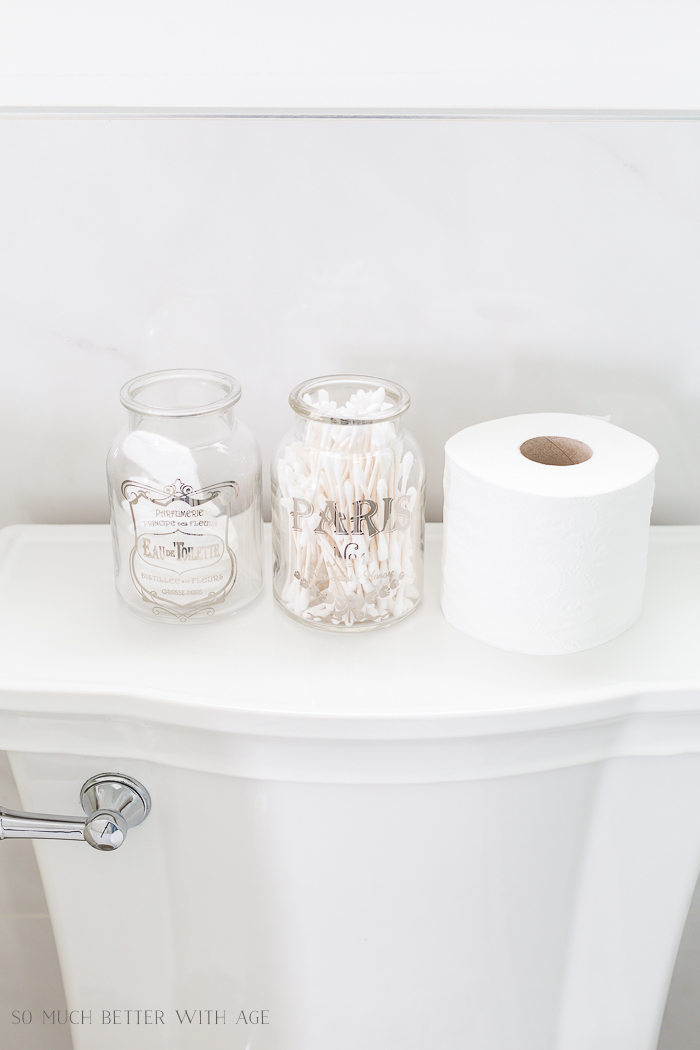 Bathroom Minimalism | How I Organize Small Bathrooms/ glass jars on back of toilet - So Much Better With Age