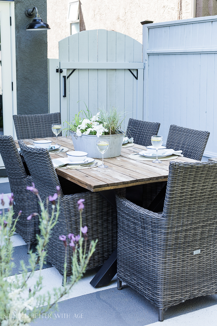 Outdoor table set for a meal with lavender and grey fence.