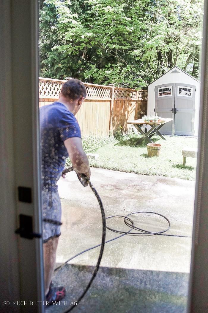 Power washing concrete patio in backyard.