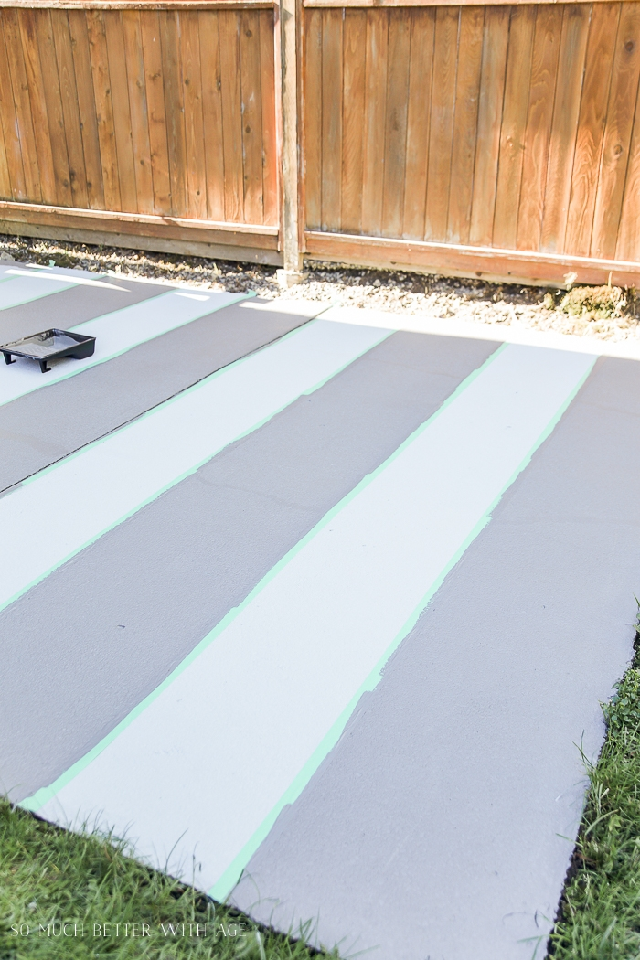 Painting stripes on concrete with a wooden fence beside it.