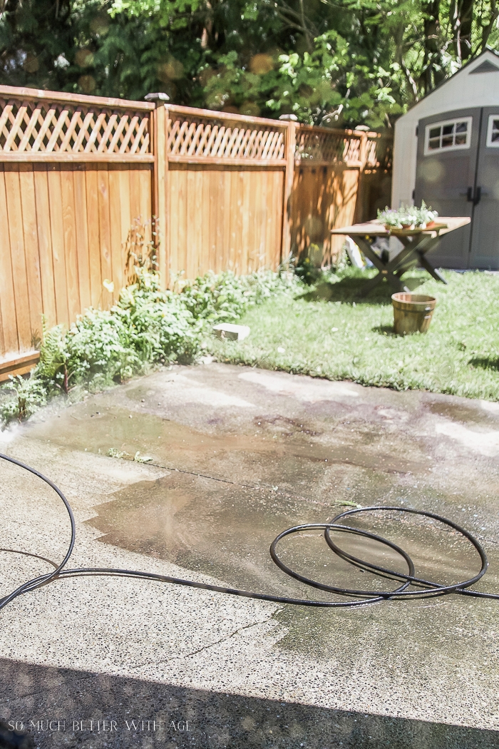 Concrete patio slab being power washed.