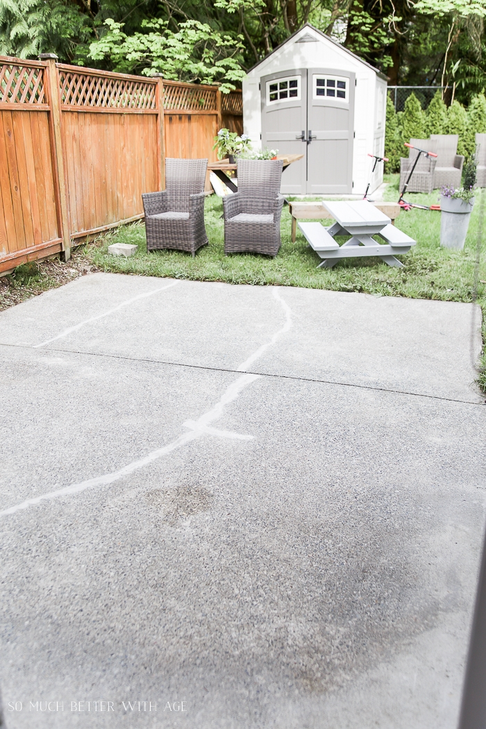 Clean concrete patio with furniture in grass in backyard.