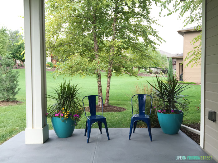 Blue chairs and planters on grey patio.