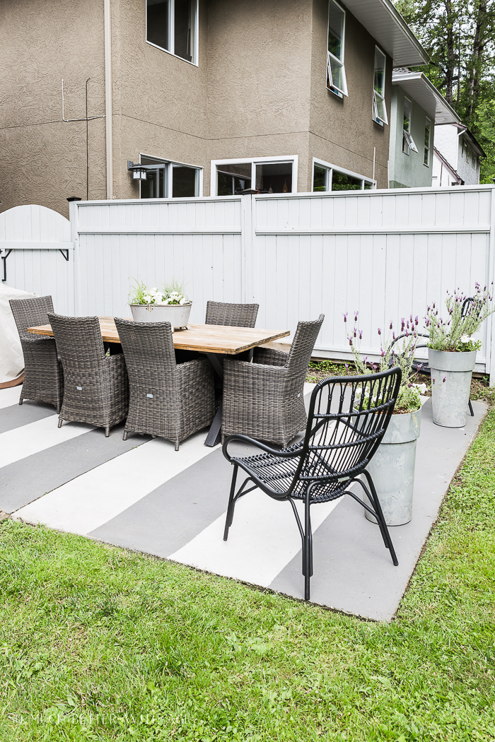 Patio table and chairs with grey fence.