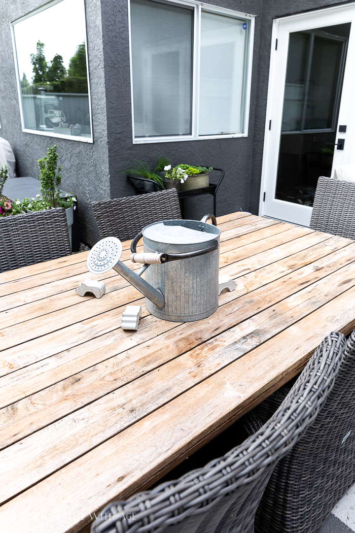 Watering can on patio table.