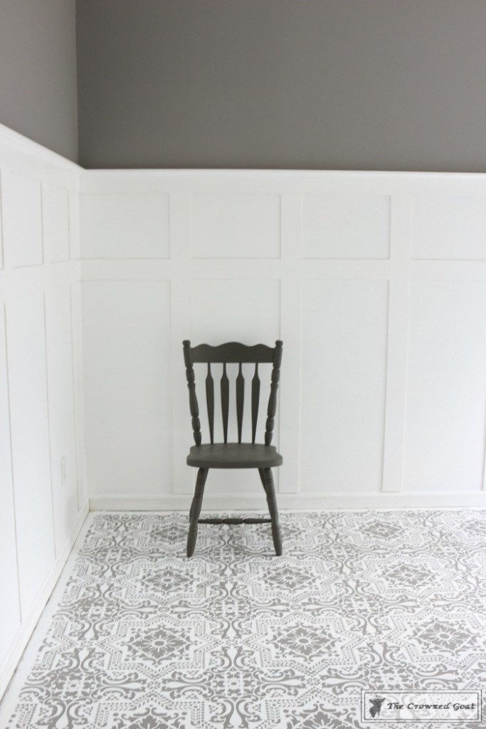 Stencilled concrete with grey walls and grey chair.