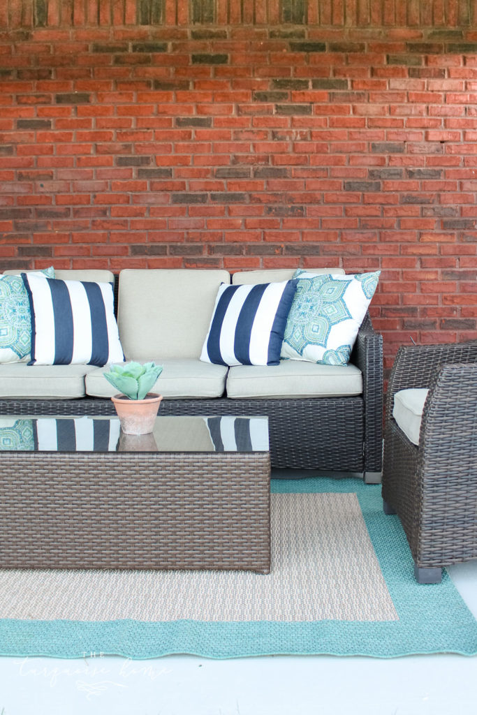 Brick wall with outdoor couch in front of it.