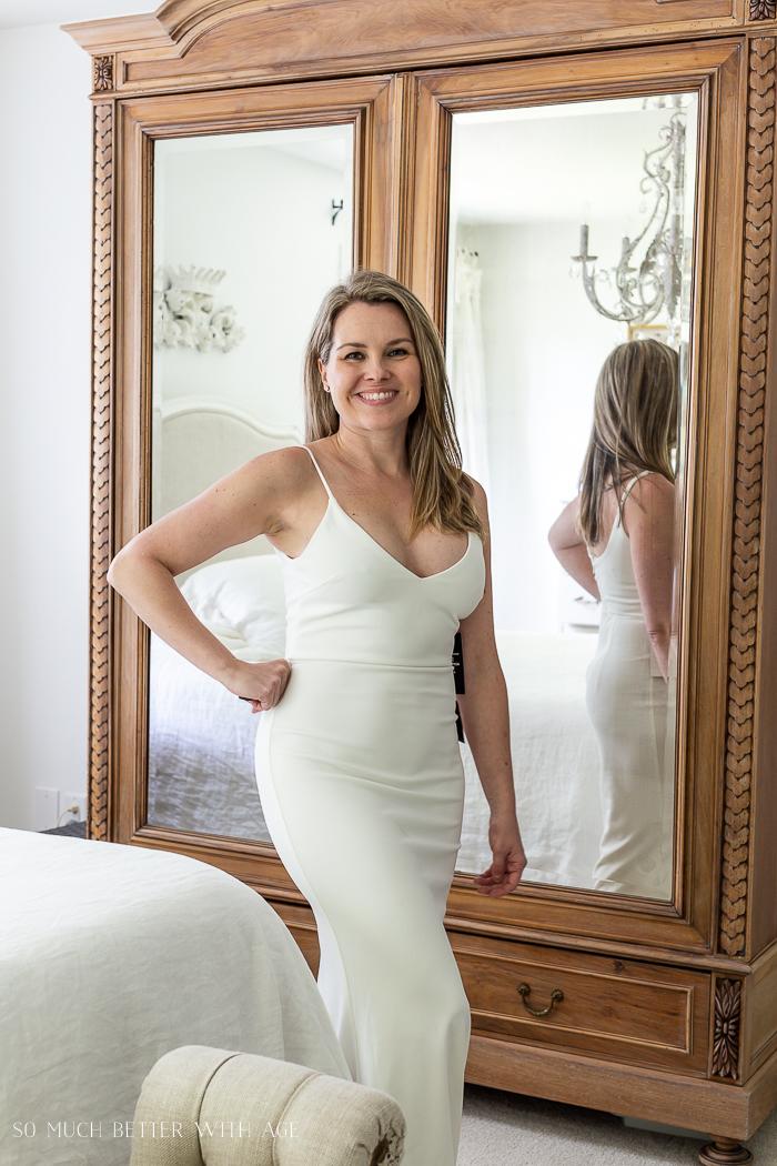 Woman smiling wearing long white dress.