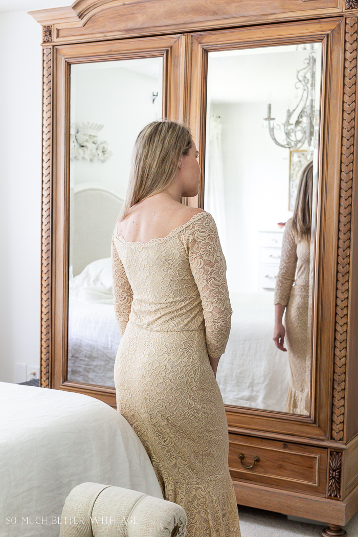 Back of lacy dress, armoire in background.