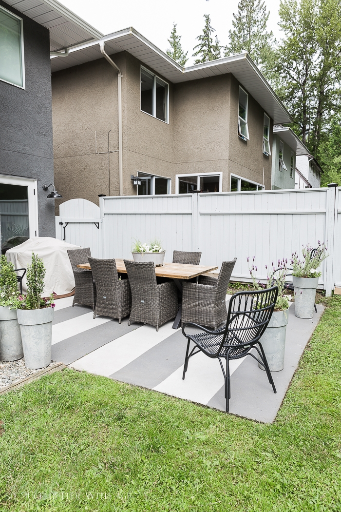 Backyard patio table and chairs with grey fence.