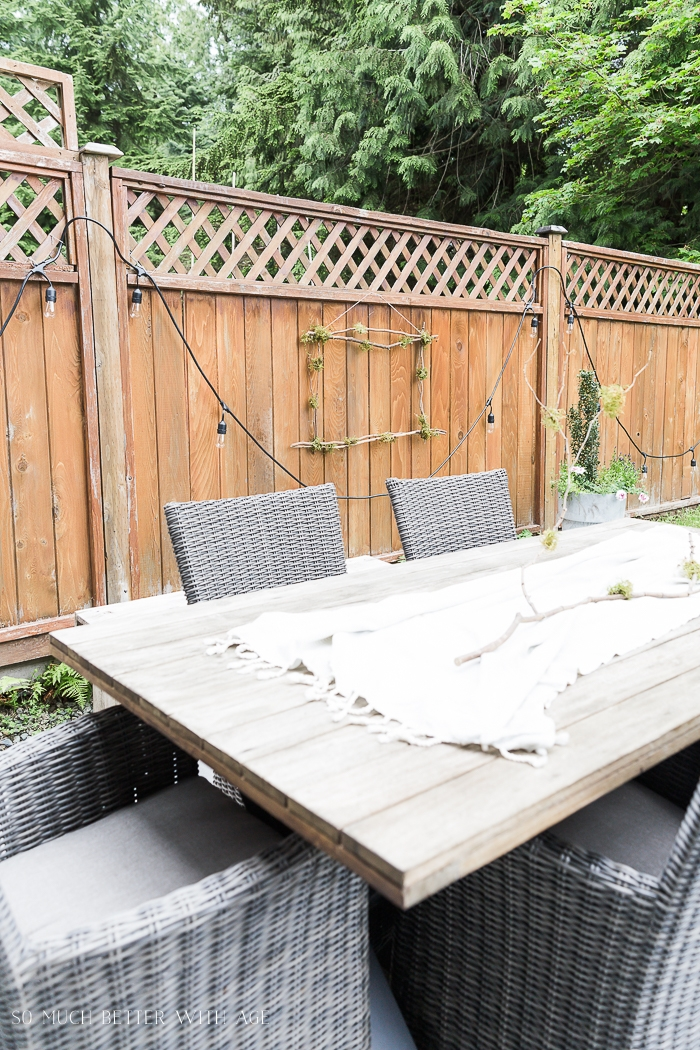 Fence with outdoor patio table and chairs.