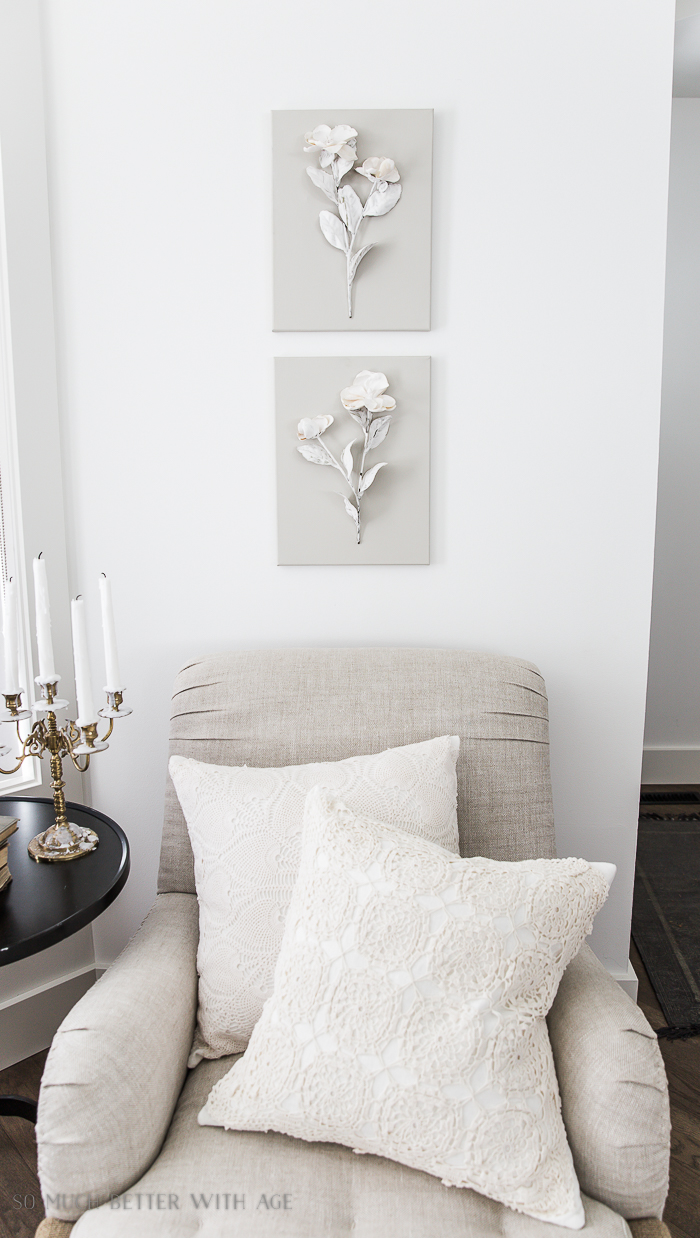 Flowers on canvas on wall, cream pillows on chair and candelabra.