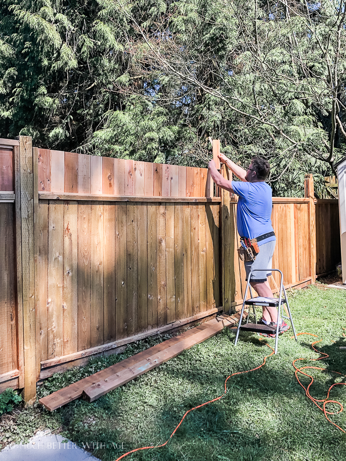 Man holding up boards to a fence.