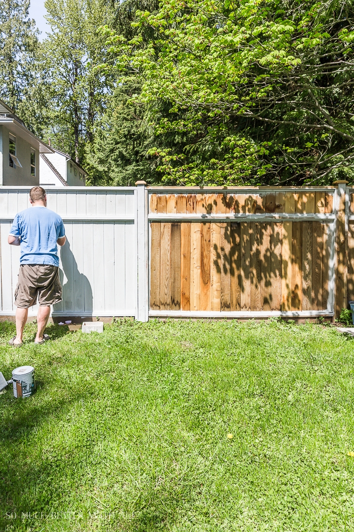 Man painting or staining a fence.