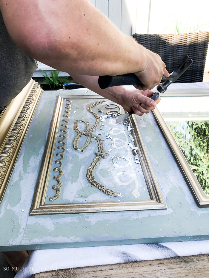 Chiselling over design on mirror.