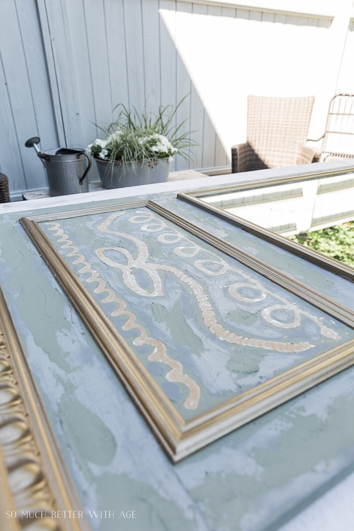 Green, gold and grey mirror laying flat on table outside.