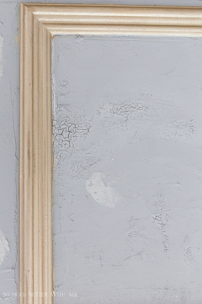 Cracks in grey paint with gold trim.