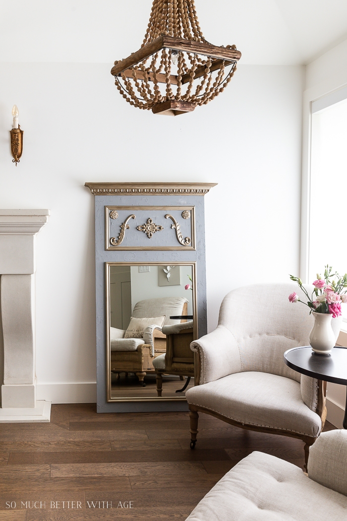 Grey and gold mirror in living room with beaded chandelier.