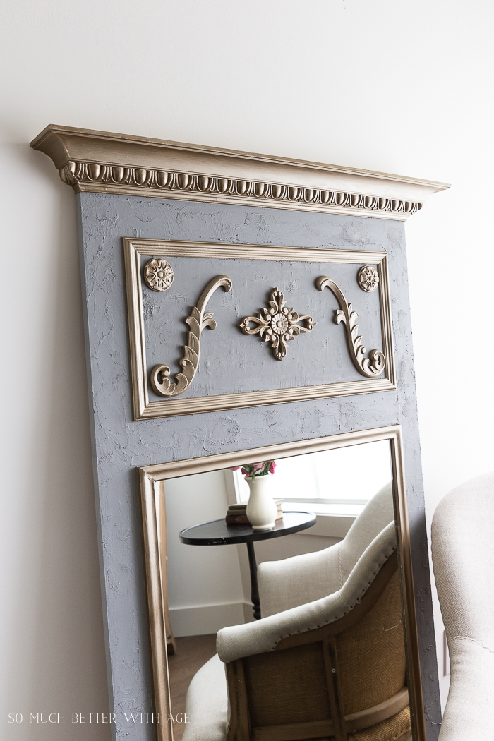 Grey mirror with gold painted appliques.