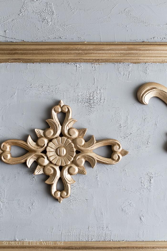 Gold appliques on plaster wall.