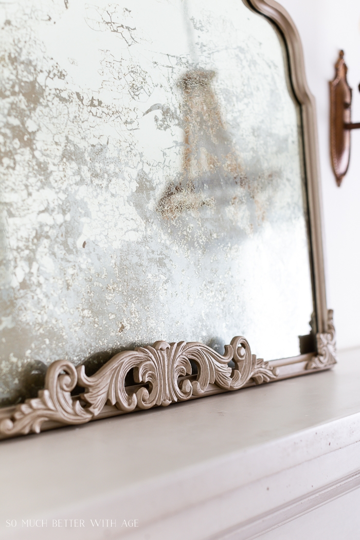 Close up of antique mirror in soft gold frame.