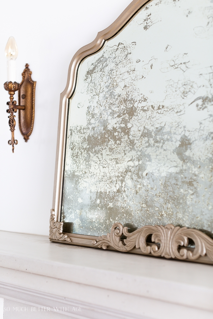 Antiqued mirror with sconce on wall.