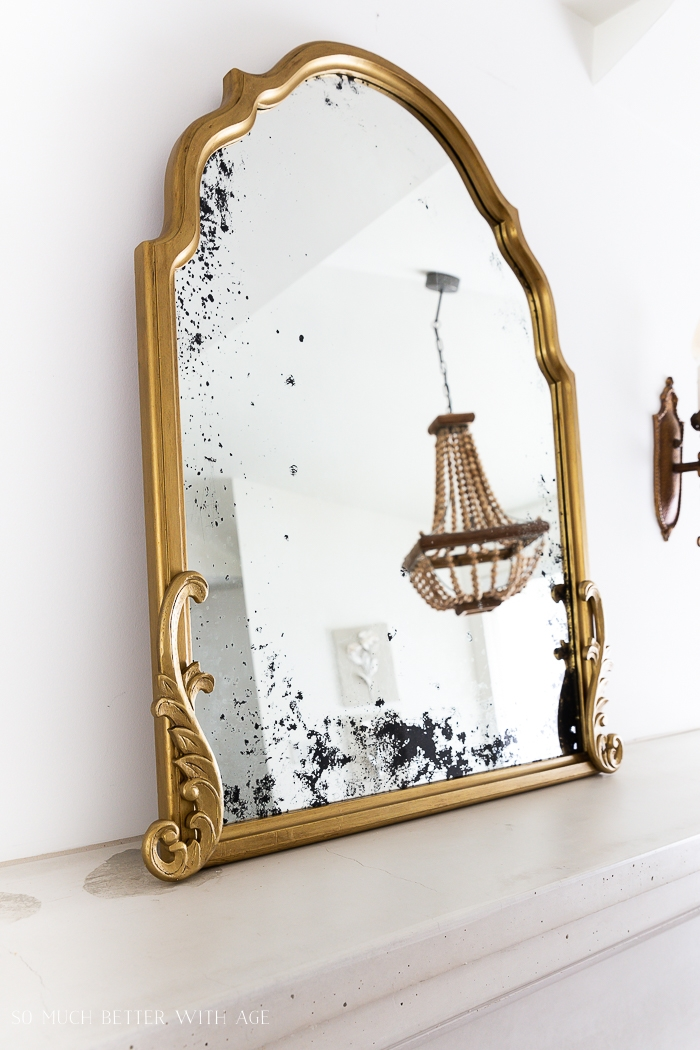 Gold mirror with image of beaded chandelier.