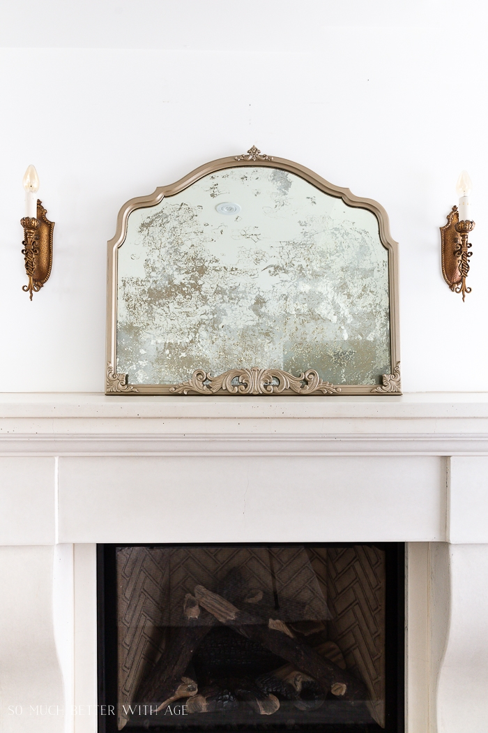 Champagne gold mirror with cool technique sitting on a fireplace mantel.