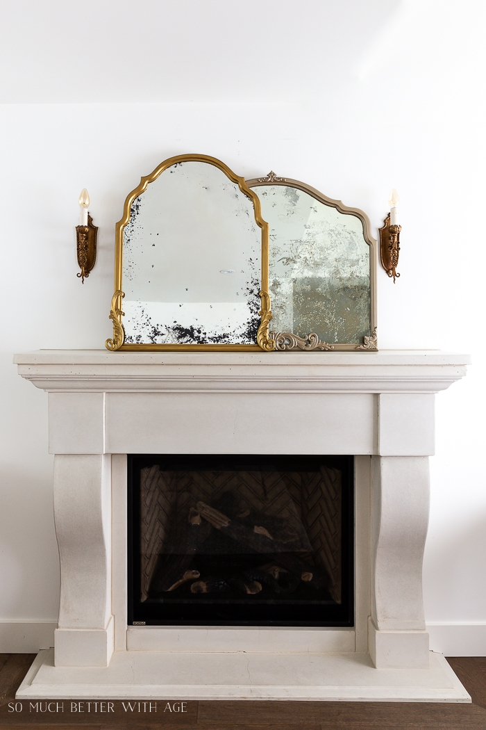 Two gold mirrors that look antique on top of fireplace mantel.