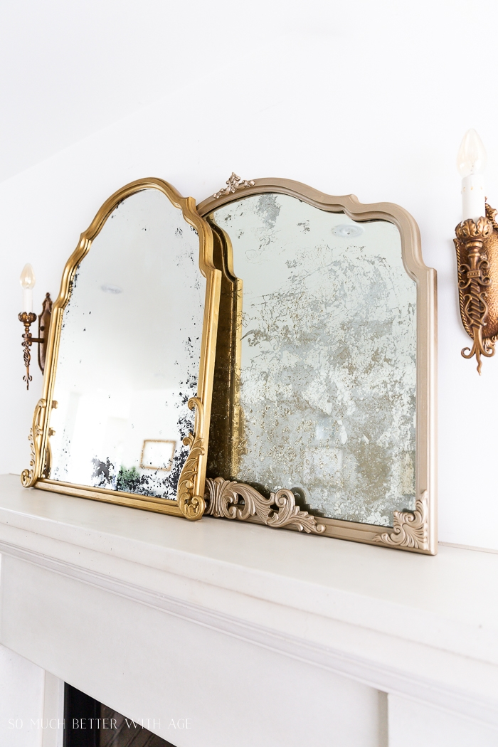 Gold mirrors in different colors on fireplace mantel.