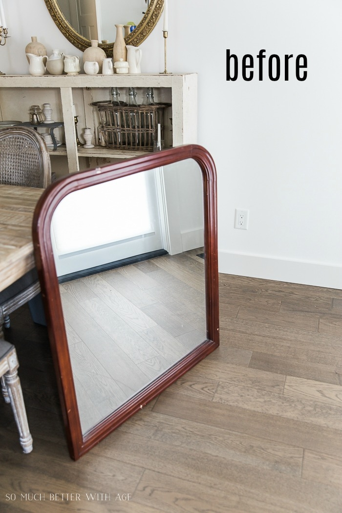Before photo of wooden mirror leaning on a dining table.