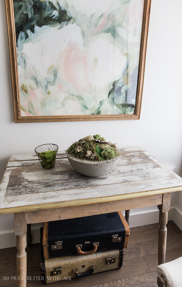 Concrete mossy bowl on table with floral artwork.