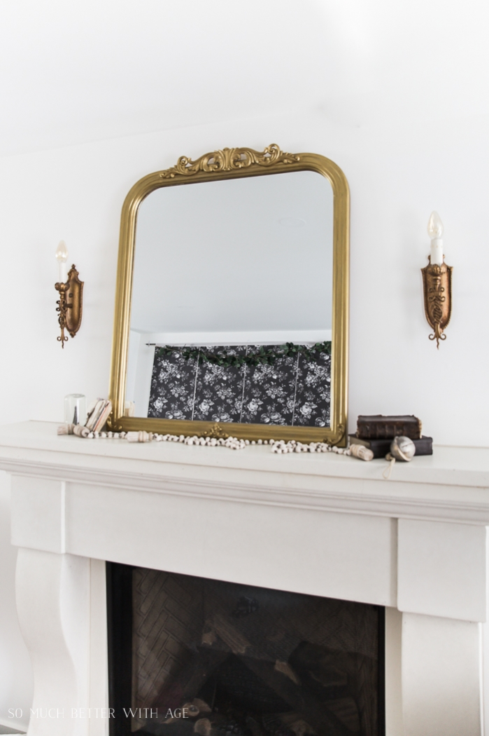 Gold mirror on top of fireplace mantel with brass wall sconces.